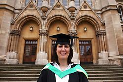 Portrait of woman in graduation gown outside university,