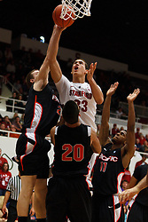 Nov 28, 2011; Stanford CA, USA;  Stanford Cardinal forward Dwight Powell (33) shoots past Pacific Tigers guard Colin Beatty (left) and over forward Ross Rivera (20) during the second half at Maples Pavilion. Stanford defeated Pacific 79-37. Mandatory Credit: Jason O. Watson-US PRESSWIRE