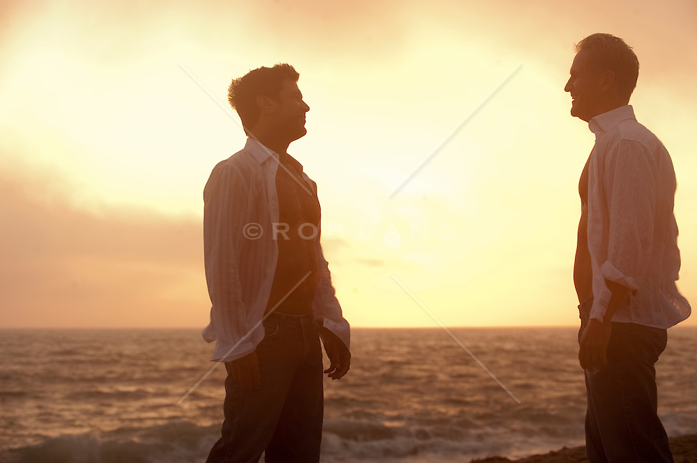 Two men looking at one another on the beach during a sunset