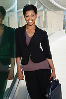 Business woman with briefcase standing outside office building, portrait