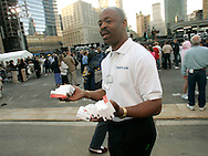 Wilmouth Seaton a Red Cross Chaplain hands out tissues to family members of victims of the World Trade Center attack at the site of the disaster on the fourth anniversary of the attack in New York September 11, 2005.