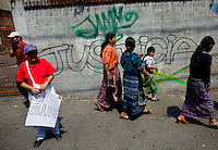 Indigenous women walk past graffiti calling for justice as citizens take to the streets as a day of protest in connection with Guatemala's President Alvaro Colom fill the Central Plaza in Guatemala City May 17, 2009. . Thousands of protesters took to the streets of the capital  Sunday in two separated rival marches, one in support of the President and one denouncing President Alvaro Colom who was accused this week of murder, money laundering and having ties with narco-traffickers.(Darren Hauck)