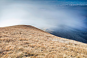 Wind blows the fog over the ridge