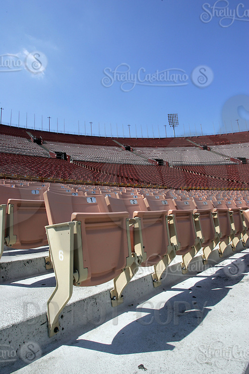 9 April 2006: Interior of the Los Angeles Memorial Coliseum empty seats at 3911 South Figueroa Street. Opened to the public in June 1923.  First football game played on October 6, 1923 by USC hosting Pomona College before a crowd of 12,836.  Hosted the Xth and XIIIrd Olympiads, Superbowl I and VII and the 1959 World Series.  Former home for the NFL LA Rams 1946-1979, MLB Dodgers 1958-1961, AFL SD Chargers, NFL LA Raiders 1982-1994. Currently serves as home field for USC Trojan football since 1923 and other current world-class events. Seats 92,516 people fans at full attendance. Stadium detail, art, graphic,stock, blue sky.