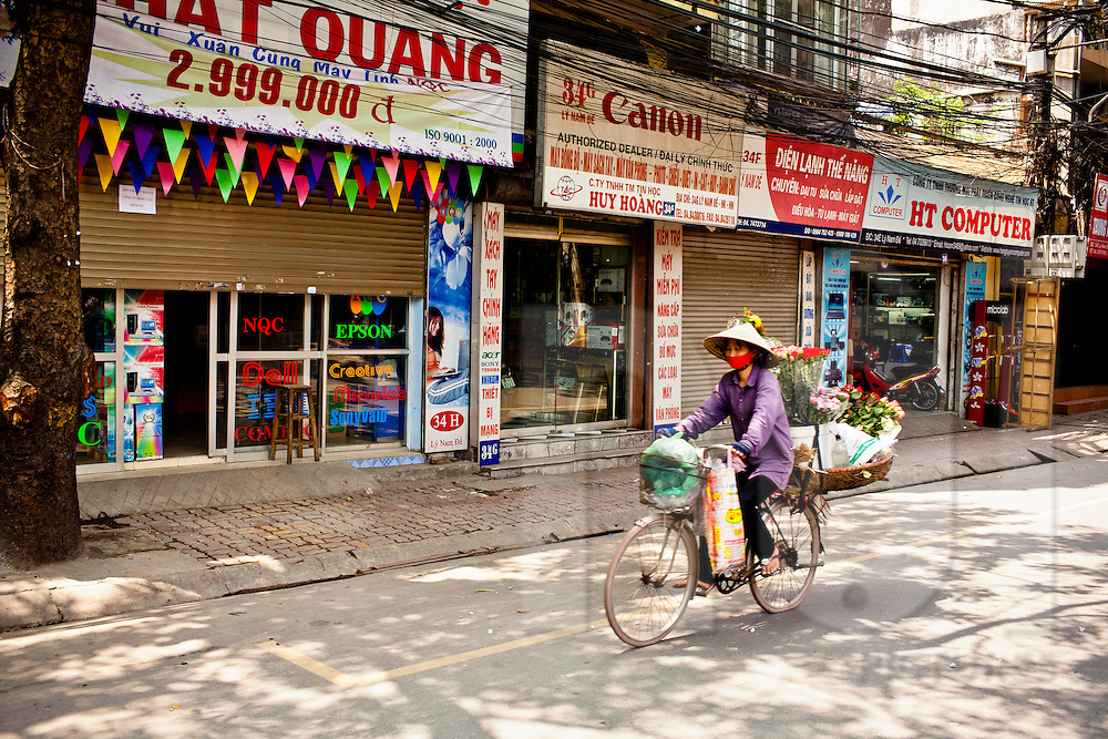 Street vendor cycles through a quiet street of Hanoi, Vietnam, Southeast Asia