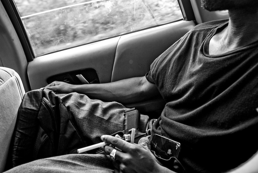 "Big Rickie keeps his handgun on his lap while driving through  Gary, Indiana.  As a matter of course, many in Gary carry handguns for personal protection. There has been a spate of murders in Gary late in the summer. Big Rickie works as a barber in Gary and is working on building his rap music collective ""Addictive Music.""  (© William B. Plowman/Redux)"