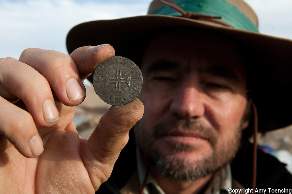 ORANJEMUND, NAMIBIA -- SEPTEMBER 24: Archeologist Dieter Noli holds a silver coin, from the the time of King John II's reign, found on site of a Portuguese shipwreck on September 24, 2008 in Oranjemund, Namibia. The wreck was discovered by miners in the Namdeb diamond mine off the coast of Namibia. The ship was found seven meters below sea level on April 1, 2008. Archeologists presume the wreck is from the early 1500s. Most of the the artifacts found are being stored in a storage shed at the Namdeb Diamond Mine. Items include: copper ingots, bronze canons, canon balls, pewter bowls and plates, ivory tusks from African elephants, and most substantial over 2000 gold coins- approximately 21 kg - the most gold found in Africa since the Valley of the Kings in Egypt. (Photo by Amy Toensing) _________________________________<br />