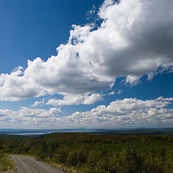 Cumulus clouds over an area on Lily Bay Mountian that has recently been logged.  Near Greenville, Maine.