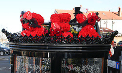 © Licensed to London News Pictures. 09/12/2015. London, UK. Red flowers spelling out the word SEX on the carriage carrying the coffin... The funeral of former brothel keeper Cynthia Payne takes place at the South London Crematorium.  In 1980 Cynthia Payne was sentenced to 18 months for running a brothel at her house on Ambleside Avenue in Streatham. It was alleged, at the time, that judges and Members of Parliament were visitors to her establishment. Photo credit: Peter Macdiarmid/LNP
