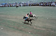 Mongolia, Ulaan Baator. July 1996: Two young horse riders race towards the finish of one of the horse races in the Naadam Festival. The annual festival celebrates the three traditional sports of horse racing, archery and wrestling.