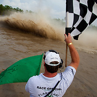 NAPLES, FL -- March 6, 2011 --  Starter Kyle Holcombe waves the checkered flag during the Swamp Buggy Races at the Florida Sports Park in Naples, Fla., on Sunday, March 6, 2011.  The races originated in the 1940's by bored hunters and draws thousands of fans three times a year to take in the buggies and jeep compete in the swamp. (Chip Litherland for ESPN the Magazine)