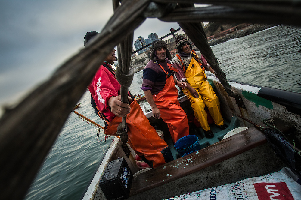 VALPARAISO, CHILE - MARCH 18, 2014: Artisanal fishermen return to port, as a crane lifts their boat out of the water in Valparaiso, Chile. PHOTO: Meridith Kohut for The World Wildlife Fund
