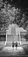 The umbrella-like trees frame a couple who are about to walk up the stone stairway that was once part of an historic home in St. Charles, IL.   Aspect Ratio 1w x 1.25h.