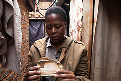 April 29, 2020, Johannesburg, Gauteng, South Africa: Linely Mwimalizani a 37 years old from Malawian National living in Itireleng Squatter Camp, Pretoria South Africa  take a pose for a  photo with  her passport as it was burned down and she doesn't have any option with no money left in the midst of lockdown in South Africa. 'I came from Malawi in 2017 and it's been 3 years now in South Africa. Where I was staying before, my house burned down and everything was gone but I was able to rescue my passport which has been burned but only few things were visible. I was about to apply for the new passport but the lock down started then couldn't do it. The border of South Africa closed and I was thinking to go back to my country when my passport will be ready  but I'm really stuck as I don't know when this lock down will be lifted so that I can apply for a new passport and  go back home. All the money I kept to apply for the new passport, I used it to survive as I'm not working. I was working as a maid but I lost the job because for the Covid 19 lock down and I don't have anything on my hand. Neither I have the money to apply for the passport nor do I have the money to eat. I have one kid and my husband left me long time ago so I don't have anyone in South Africa whom I can ask for help in this difficult situation. One of my neighbors gave me on Maze Meal when the lock down started but now it's about to finish and I really don't have no plan where can I get food for my child. I don't know what to do, whom to ask? There are NGOS who came for food distribution but there are so many different nationalities here and it only covers few so I didn't able to get nothing. If the situation will be like this then we need to starve as I can see there are no any responsibilities taken my Malawian Government or the South government for foreign nationals so far.' (Credit Image: © Manash Das/ZUMA Wire/ZUMAPRESS.com)