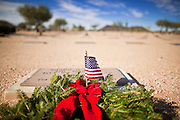09 DECEMBER 2011 - PHOENIX, AZ:  A Christmas wreath on a veteran's grave in the National Cemetery in Phoenix. Several hundred volunteers and veterans gathered at the National Memorial Cemetery of Arizona in Phoenix Saturday to lay Christmas wreaths on headstones, a tradition started by Wreaths Across America. Wreaths Across America is a nonprofit organization founded to continue and expand the annual wreath laying ceremony at Arlington National Cemetery begun by Maine businessman, Morrill Worcester, in 1992.  PHOTO BY JACK KURTZ