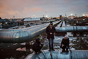 Teenagers hang out on heating pipes which run through much of the older right bank of Astana, in Kazakhstan.