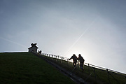 Visitors climb and descend the steep gradient of 225 steps, 43 metre high Waterloo Lion's battlefield Mound, on 25th March 2017, at Waterloo, Belgium. The Lion's Mound (Butte du Lion is a large conical artificial hill completed in 1826. It commemorates the location on the battlefield of Waterloo where a musket ball hit the shoulder of William II of the Netherlands (the Prince of Orange) and knocked him from his horse during the battle. From the summit, the hill offers a 360 degree vista of the battlefield. The Battle of Waterloo was fought 18 June 1815. A French army under Napoleon Bonaparte was defeated by two of the armies of the Seventh Coalition: an Anglo-led Allied army under the command of the Duke of Wellington, and a Prussian army under the command of Gebhard Leberecht von Blücher, resulting in 41,000 casualties.