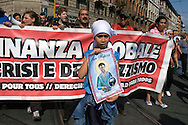 Roma 30 Maggio 2009.Manifestazione  dei No Global  per protestare contro il G8 e le politiche sull'immigrazione del Governo Berlusconi..Demonstrators march through the street of Rome to protest against a meeting of the Group of Eight (G8) interior and justice ministers taking place in the Italian capital.A demonstrator holds a placard reading 'Saint Papier, patron of the migrants of the world'.