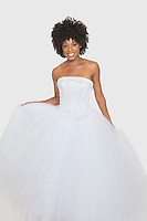 Portrait of beautiful African American bride in white wedding dress standing against plain background