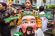 "05 JULY 2014 - BANGKOK, THAILAND:  A man carries a Chinese style head during a parade for vassa in Bangkok. Vassa, called ""phansa"" in Thai, marks the beginning of the three months long Buddhist rains retreat when monks and novices stay in the temple for periods of intense meditation. Vassa officially starts July 11 but temples across Bangkok are holding events to mark the holiday all week.   PHOTO BY JACK KURTZ"