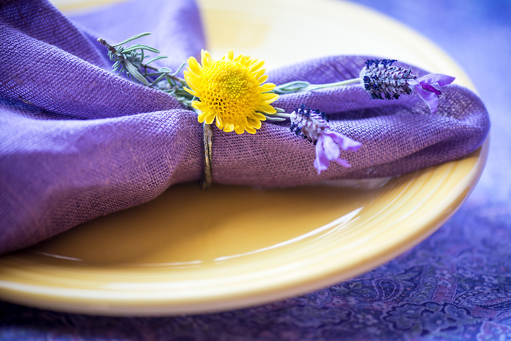 Yellow plate with purple lavender, napkin and yellow flower.