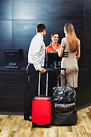 Businessman and businesswoman attending and checking in hotel