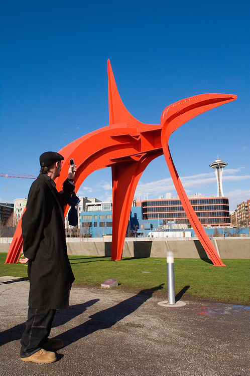 """Visitor taking photo with cell phone of Alexander Calder's """"Eagle"""" in the Seattle Art Museum's Olympic Sculpture Park with the Space Needle in the distance; Seattle, Washington."""