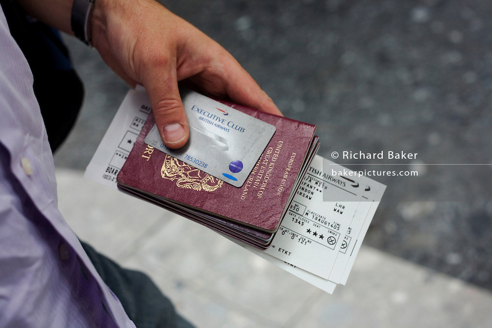 "A close-up detail of a male passenger's hand that holds on to his family's travel documents before proceeding to his British Airways check-in zone at Heathrow Airport's Terminal 5. With a Silver company Executive 'One World' loyalty card, his ticket and British passport to hand, he waits in line after registering at a self-service kiosk where his seat has been designated. A BA employee then only needs to take his luggage. From writer Alain de Botton's book project ""A Week at the Airport: A Heathrow Diary"" (2009)"