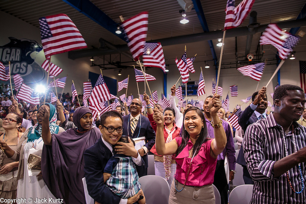 04 JULY 2012 - PHOENIX, AZ: LUIGE DEL PUERTO holds his son, SOL ELIJAH DEL PUERTO, after they and his wife, PEARL DEL PUERTO were naturalized US citizens Wednesday. They are originally from the Philippines. About 250 people, from 62 countries, were naturalized as US citizens during the 24th Annual Fiesta of Independence naturization ceremony at South Mountain Community College in Phoenix Wednesday. The ceremony was presided over by the Honorable Roslyn O. Silver, Chief United States District Court Judge.    PHOTO BY JACK KURTZ