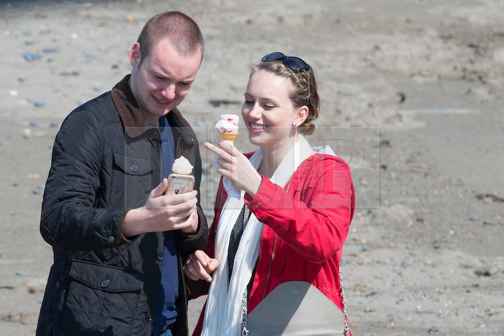 © Licensed to London News Pictures. 12/05/2016. Aberystwyth, Wales, UK. A young couple take a 'selfie' as they eat ice cream at the seaside in  Aberystwyth on the  last day of warm weather in the current mini-heatwave.   The temperatures are set to fall over the coming days, with bright but colder conditions prevailing over the country .  Photo credit: Keith Morris/LNP