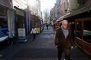 Een man loopt door de Mariastraat in Utrecht door de zon.<br /> <br /> A man is walking in the Mariastraat in Utrecht.