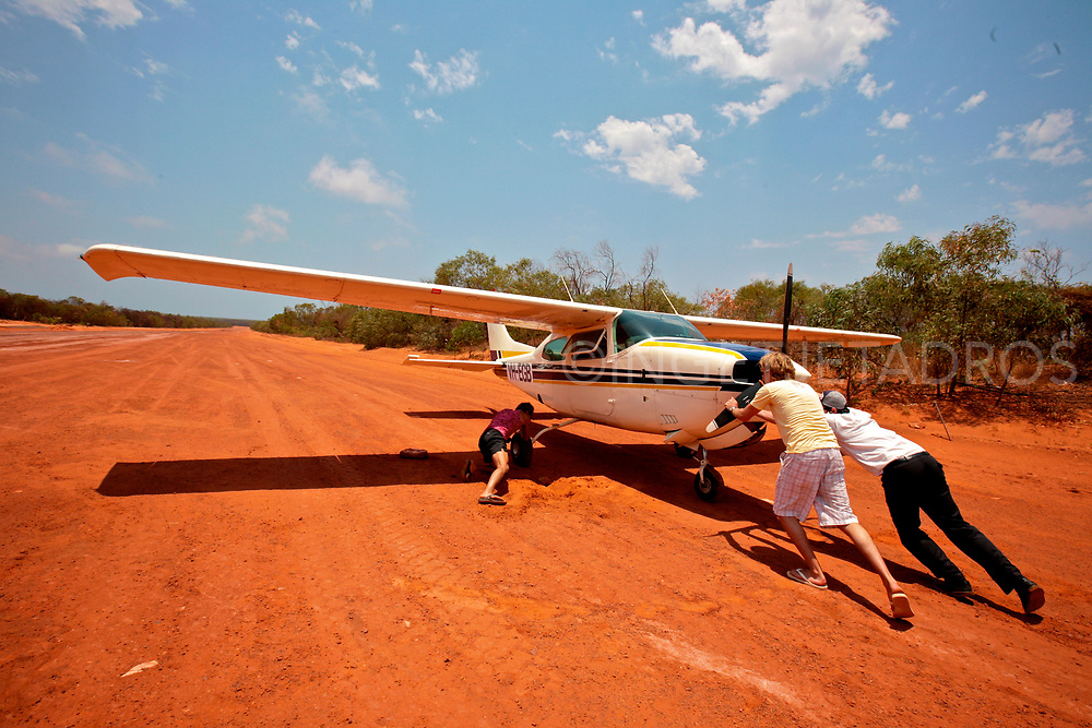 Pilot and passengers pushing a bogged airplane at the Cape Leveque airstrip, Dampier Peninsula, WA