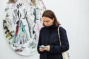 "New York, NY - 5 May 2017. The opening day of the Frieze Art Fair, showcasing modern and contemporary art presented by galleries from around the world, on Randall's Island in New York City. A woman checks her phone in front of a painting by Paulina Ołowska, ""I need to introduce you to each other—you've got so much in common,"" in the Foksal Gallery Foundation booth."