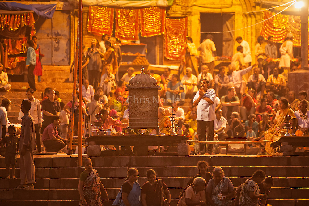 Worshipers at the fire puja ceremony held at the Mani Karnika (Main) Ghat along the Ganges in the Old City of Varanasi India.