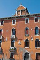Orange building facade against a blue sky in Venice, Italy