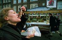 January 1991, Amsterdam, Netherlands --- A woman eats Dutch herring in Amsterdam, Netherlands --- Image by © Owen Franken/CORBIS