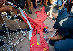 Tuen Mun, Hong Kong. 22 September 2019. Pro democracy demonstration and march through Tuen Mun in Hong Kong. Marchers protesting against harassment by sections of the pro Beijing community. Largely peaceful march had several violent incidents with police using teargas. Several arrests were made. Pictured;  Chinese flag ripped and burned. Iain Masterton Live News.
