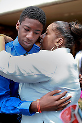 14 May 2014. New Orleans, Lousiana. <br /> Lamichael Jackson 15 yrs is comforted by a relative at the funeral of his 14 year old brother Miqual Jackson at the New Hope Baptist Church. Miqual Jackson was shot in the back of the head May 5th and died shortly afterwards. Surviving brother Lamichael was shot in the leg. 52 year old Gregory Johnson is wanted on 1st degree murder charges. Randy Pittman, 49, an associate of Johnson's was arrested on 3 counts of being a principal to 1st degree murder. The New Hope Baptist Church witnessed the funeral of 1 year old Londyn Samuels who was also gunned down in cold blood on the streets of New Orleans 8 months ago..<br /> Charlie Varley/varleypix.com