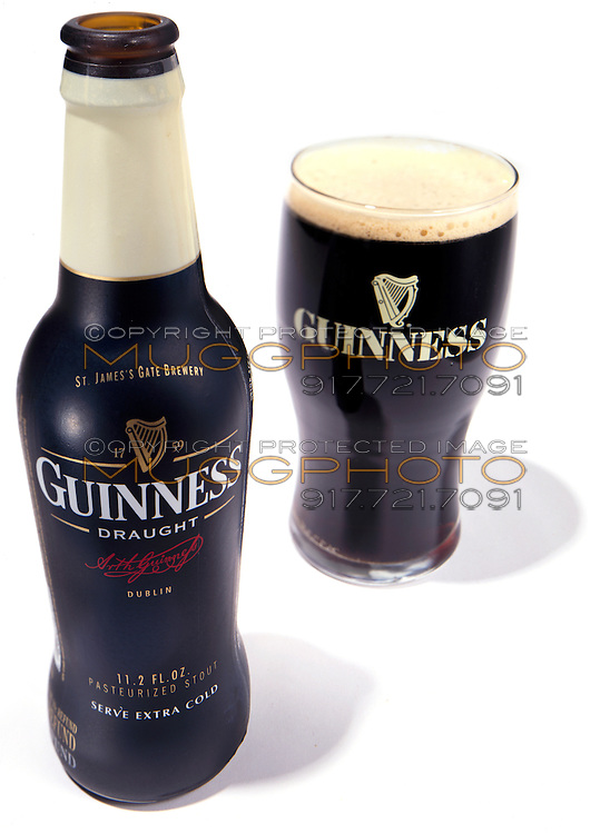 Guinness beer bottle and glass on white background