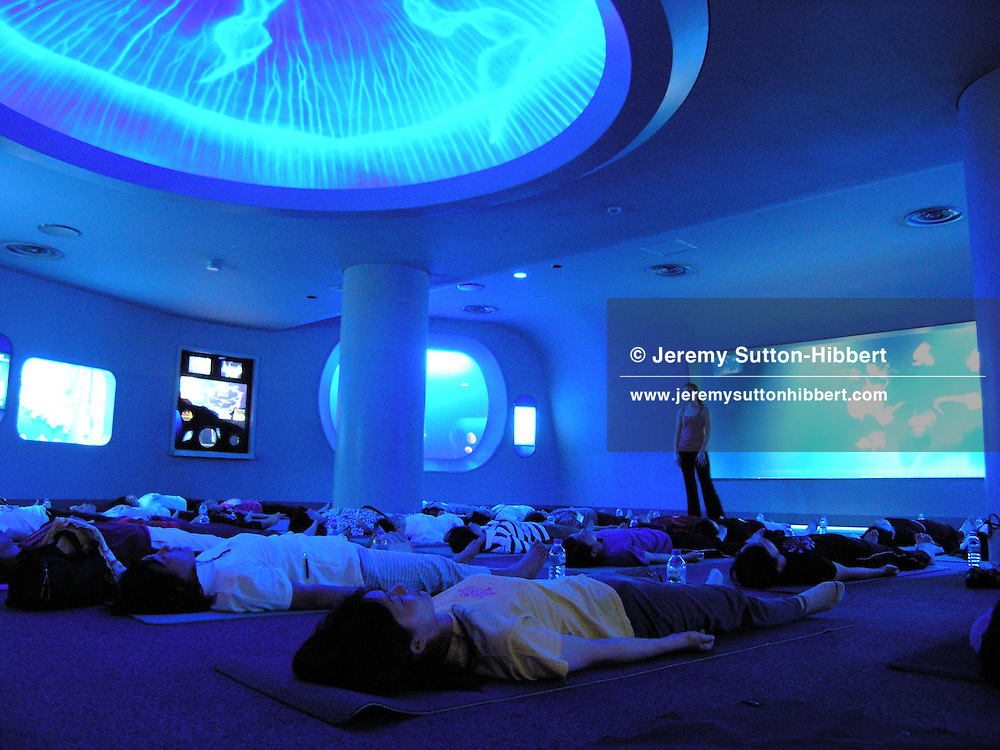 'Jellyfish Healing Night' for women in the jellyfish room in the Enoshima Aquarium, in Enoshima, near Tokyo, Japan. (undated handout photos, 2006).  The Enoshima Aquarium runs a 'Jellyfish Healing Night' for women, which involves women, relaxing and sleeping over inside the aquarium beside the tanks of jellyfish. The 30 women, who are chosen via a lottery system from more than 550 applicants, also have massage classes and yoga beside the tanks of jellyfish. Within Japan many women now wish to keep jellyfish at home as a form of therapy and relaxation, and frequently ask for advice from the Enoshima Aquarium. (Enoshima Aquarium, HO/WpN)