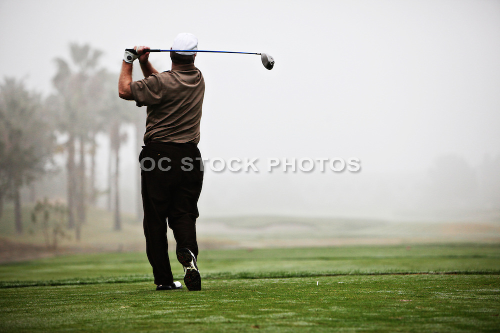 Golfer Teeing Off On A Misty Morning