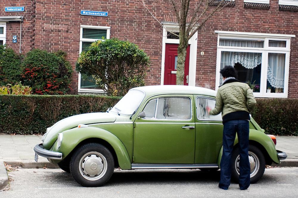 Een vrouw krabt de ruiten  van haar Volkswagen Kever. De winter is in het land