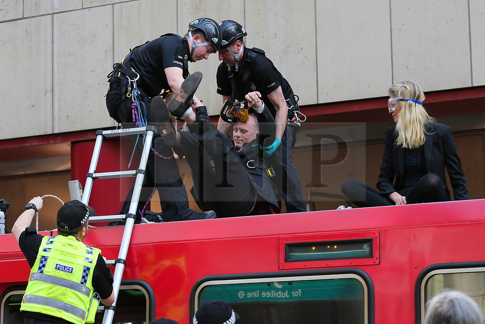 © Licensed to London News Pictures. 17/04/2019. London, UK. British Transport Police officers carries an environmental activist from the Docklands Light Railway at Canary Wharf station on day three of Extinction Rebellion Climate Change protest demanding decisive action from the UK Government on the environmental crisis.<br />  Photo credit: Dinendra Haria/LNP