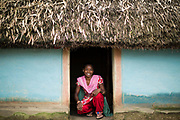 Cheerful Manjali Hasda in the doorway of her village home.