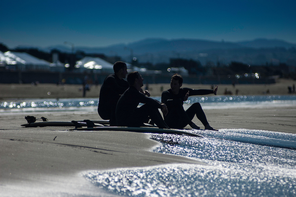 Three surfers spin yarns about their respective sessions in Ocean Beach, California.