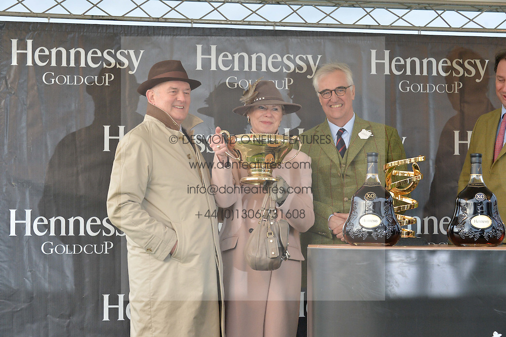 Left to right, TRISH & PETER ANDREWS owners of the 2015 Hennessy Gold Cup winner Smad Place receive the Hennessy Gold Cup from MAURICE HENNESSY at the 2015 Hennessy Gold Cup held at Newbury Racecourse, Berkshire on 28th November 2015.