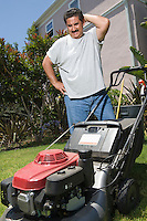 Man observing lawn mower in garden