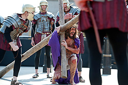 © London News Pictures. 06/04/2012. London, UK.  An actor playing Jesus carrying the cross during a performance of  The Passion of Jesus  in front of thousands of people in Trafalgar Square in central London, England on  April 6, 2012  to mark Good Friday. The actors come from the Wintershall Estate in Surrey. Photo credit :  Ben Cawthra/LNP
