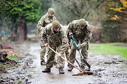 © Licensed to London News Pictures. 11/12/2015. Keswick UK.  Soldiers from the 2nd Battalion Duke of Lancaster Regiment clear pathways of mud after this weeks flooding in Keswick. Photo credit: Andrew McCaren/LNP