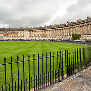 A large grassed park in front of the Royal Crescent in Bath, Somerset. The Royal Crescent is a street of 30 terraced houses laid out in a sweeping crescent in the city of Bath, England. Designed by the architect John Wood the Younger and built between 1767 and 1774, it is among the greatest examples of Georgian architecture to be found in the United Kingdom and is a Grade I listed building. Although some changes have been made to the various interiors over the years, the Georgian stone façade remains much as it was when it was first built.